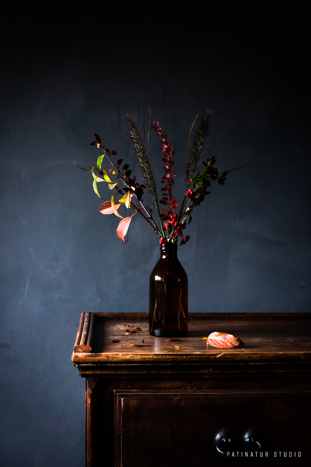 Photo art | Dark and moody still life with branches with leaves in autumn colours and Pennisetum in brown glass bottle