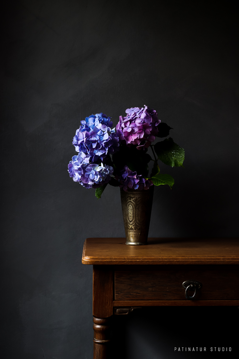 Photo art | Dark and moody still life with blue and pink hydrangeas in Indian lassi cup on wooden vintage side table