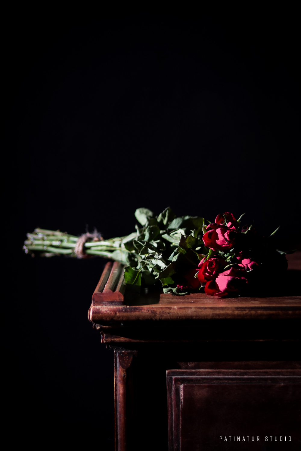 Photo art | Dark and moody still life with red rose bouquet lying on wooden sideboard