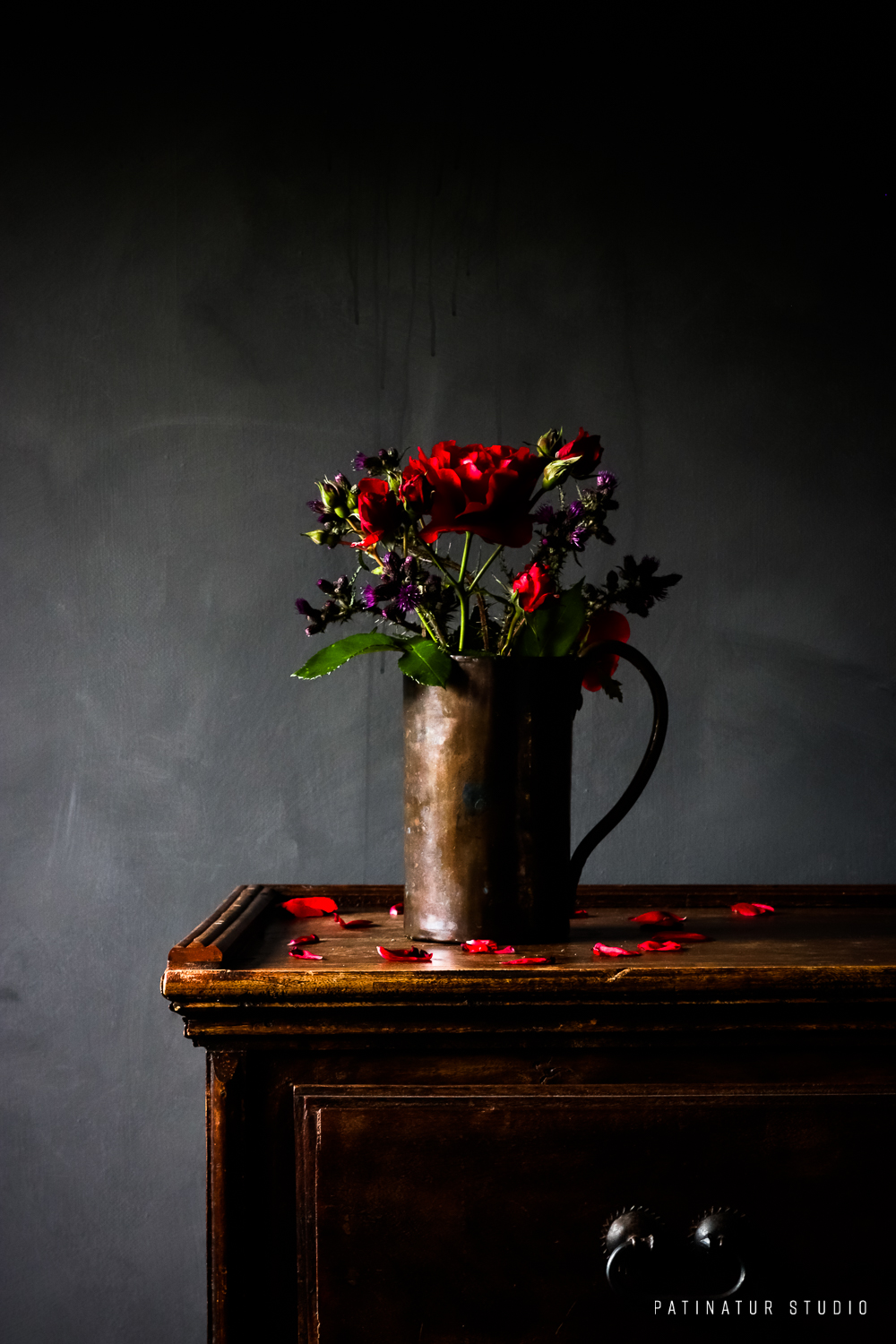 Photo art |Dark and moody still life with red roses and thistles in copper jug.