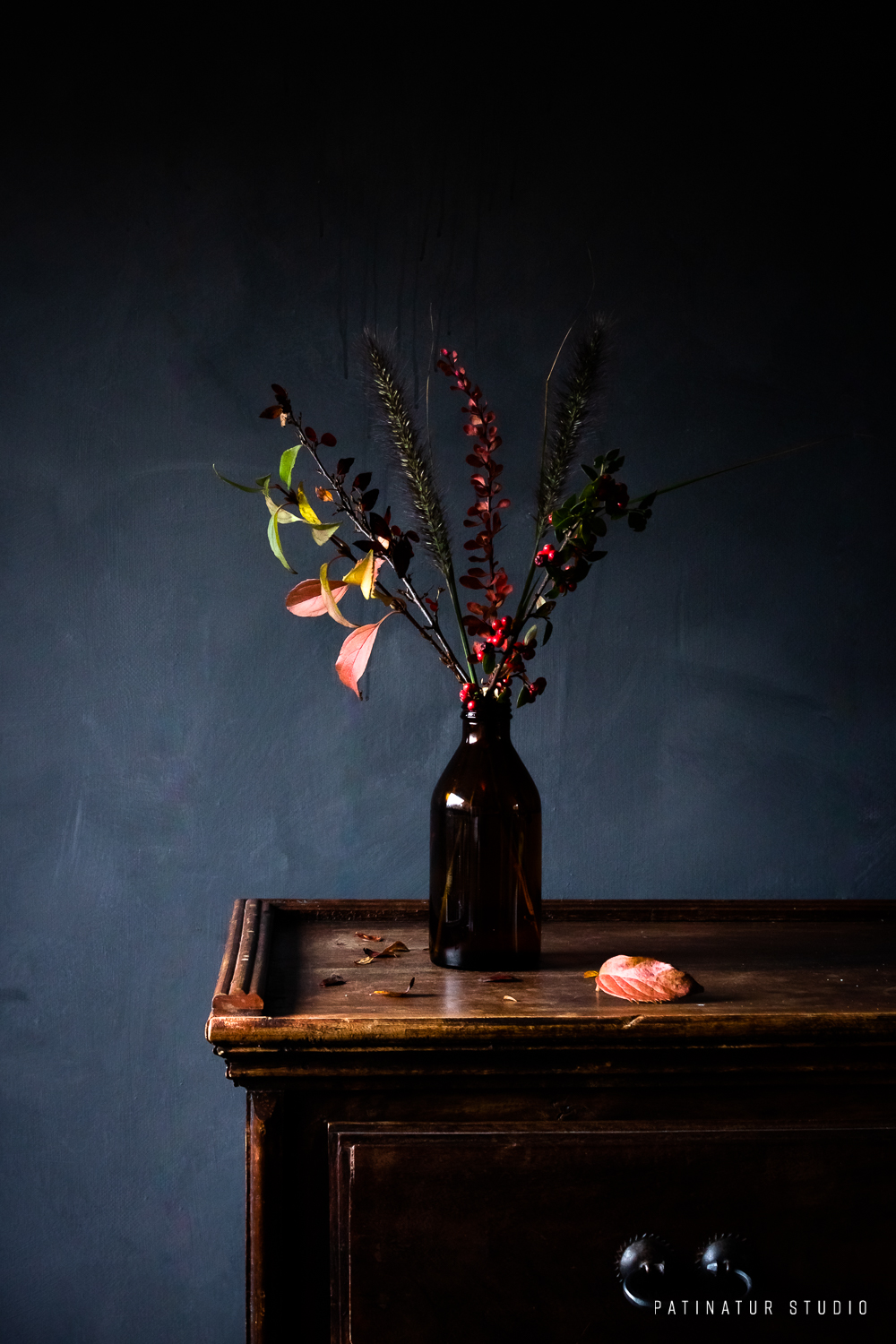 Dark and moody still life photo with bouquet of branches with autumn colours and berries.