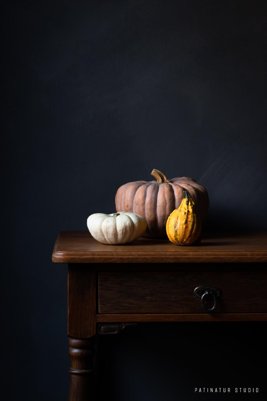 Dark and moody still life photo with pumpkins.
