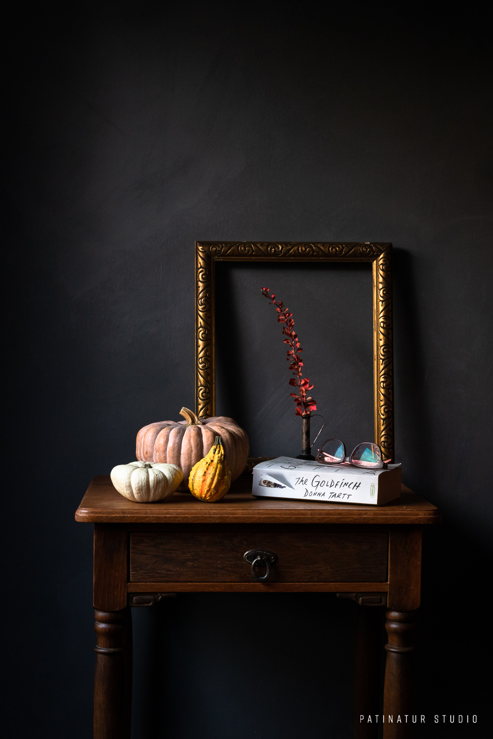 Dark and moody still life with pumpkins, autumn colours and book.