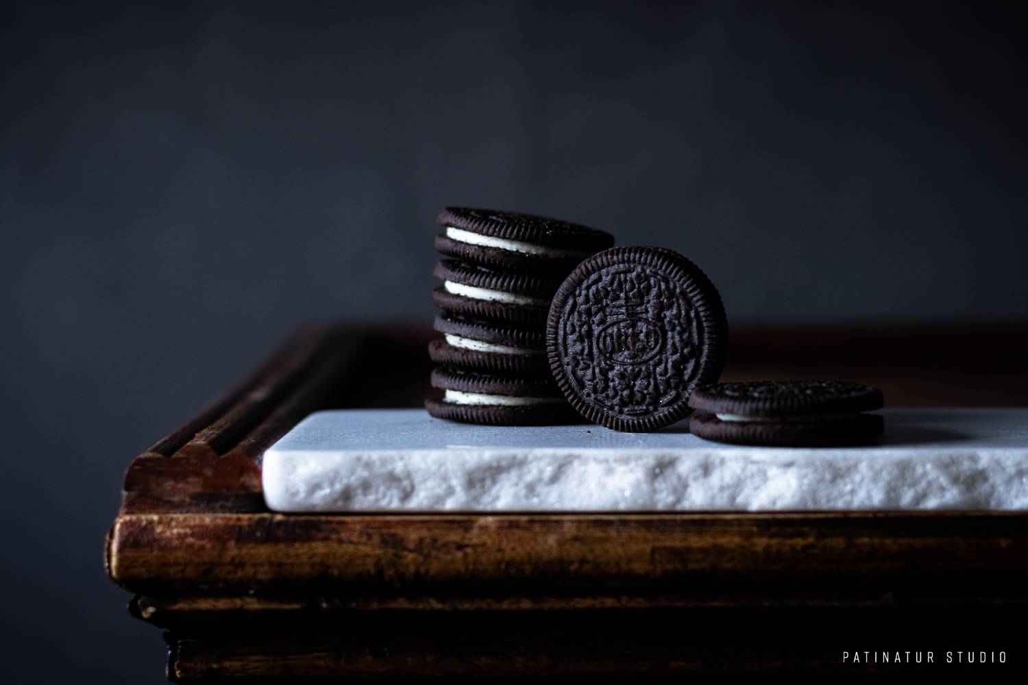 Photo art | Dark and moody still life with Photo art | Dark and moody still life with Oreos on white marble chopping board