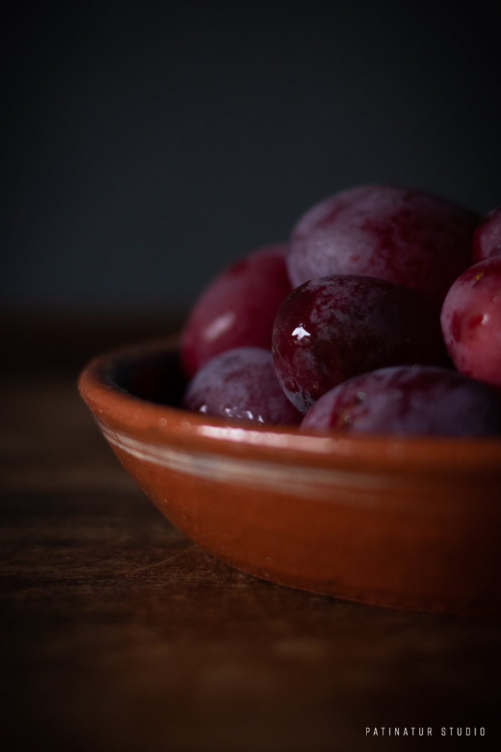 Photo art | Dark and moody still life with plums i rustic terracotta bowl