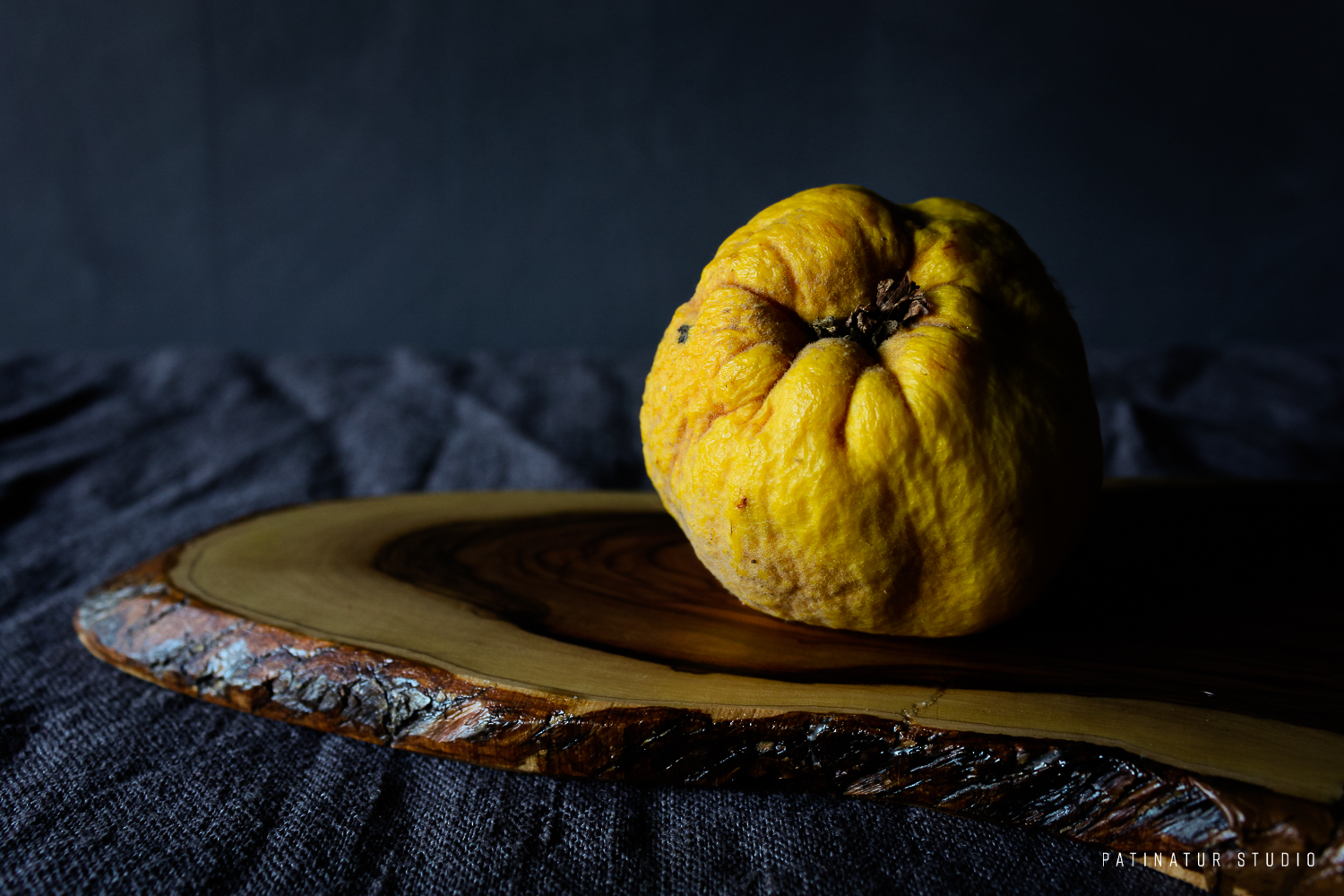 Photo art | Dark and moody still life with quince on olive wood cutting board