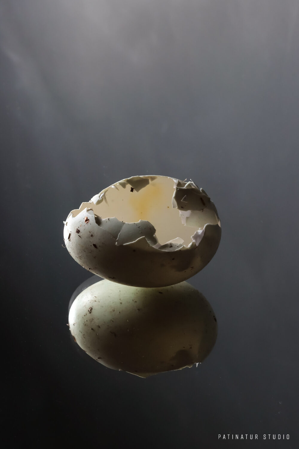 Photo Art | Dark and moody still life with with cracked egg and its reflection