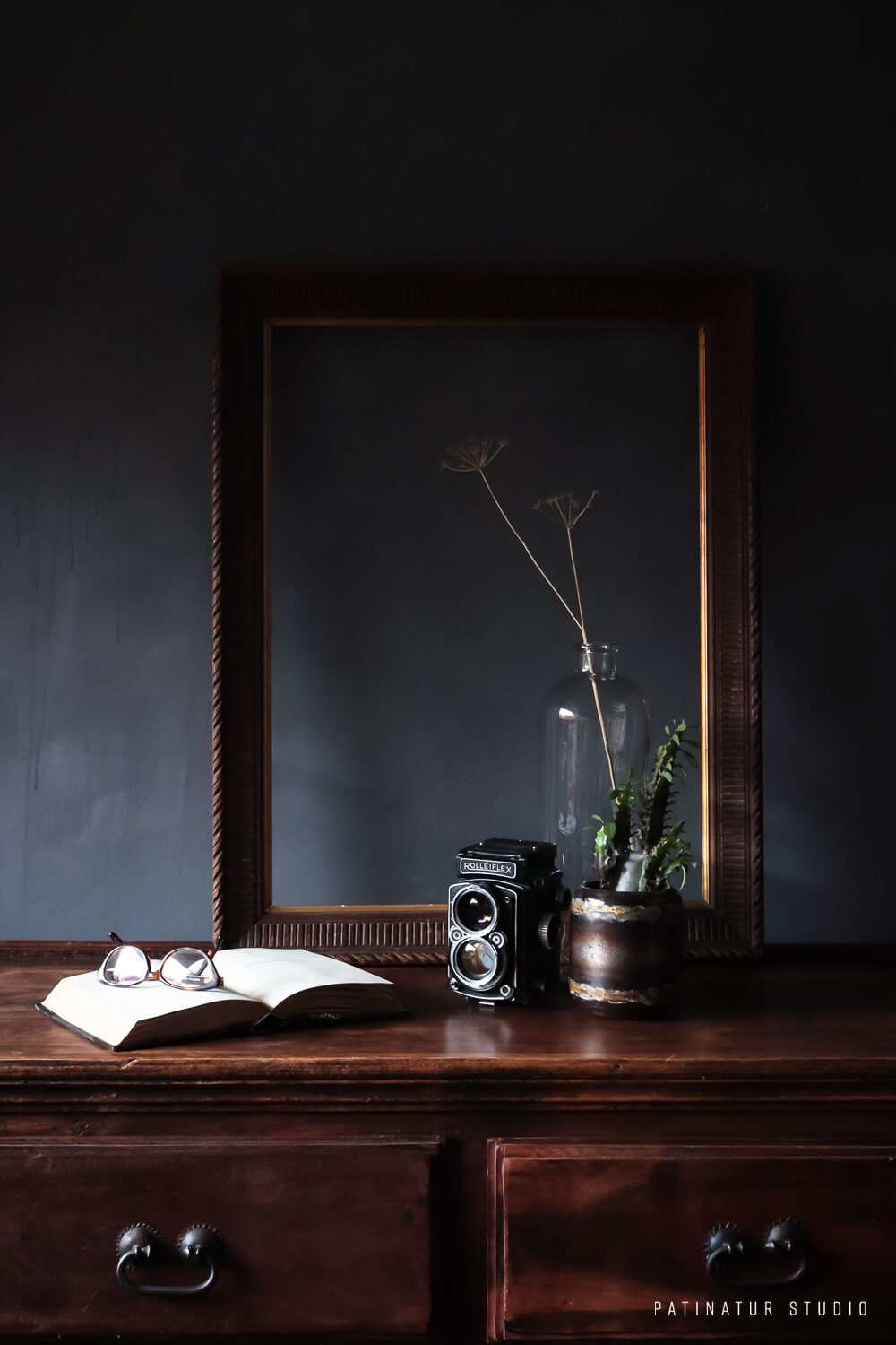 Photo Art | Dark and moody still life with vintage frame, camera and book